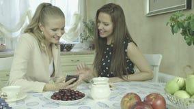 Dos mujeres jovenes sonrientes en las fotos de observación de la mesa de comedor en el teléfono móvil almacen de video