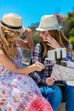 Dos mujeres jovenes sonrientes que se sientan en una ciudad bench la fabricación de caras mientras que toman los autorretratos ju Fotografía de archivo