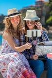 Dos mujeres jovenes sonrientes que se sientan en una ciudad bench la fabricación de caras mientras que toman los autorretratos ju Foto de archivo libre de regalías