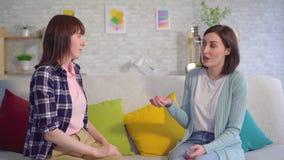 Dos mujeres jovenes sordas hermosas que hablan con lenguaje de signos en el cierre de la sala de estar para arriba almacen de metraje de vídeo