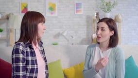 Dos mujeres jovenes sordas hermosas que hablan con lenguaje de signos en la sala de estar en casa almacen de video