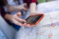 Dos mujeres jovenes turísticas usando su teléfono móvil en la ciudad Foto de archivo libre de regalías