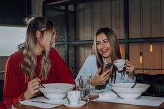 Dos mujeres jovenes usando el teléfono móvil mientras que come junto en un restaurante imagen de archivo