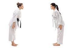 Dos mujeres jovenes vestidas en los kimonos que arquean el uno al otro Imagen de archivo libre de regalías