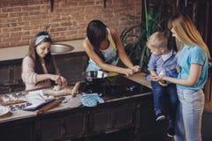 Dos mujeres jovenes y dos niños se divierten en la cocina fotos de archivo