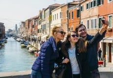 Dos mujeres jovenes y el hombre capturan un selfie feliz en un puente en Murano cerca de Venecia, Italia Foto de archivo libre de regalías
