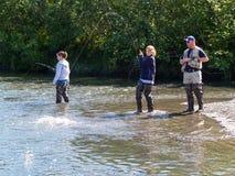 Dos mujeres jovenes y un hombre dirigen la pesca de color salmón en el pequeño río adentro Fotos de archivo