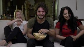 Dos mujeres jovenes y un hombre ven la TV juntos y tienen un rato maravilloso que ríe difícilmente almacen de metraje de vídeo