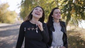 Dos mujeres largas hermosas del pelo que caminan en parque floreciente de la primavera y que discuten el último chisme El hablar  metrajes