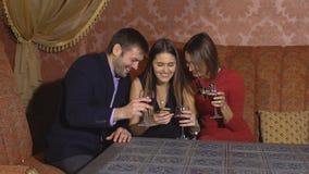 Dos mujeres lindas y un hombre que se sienta en un restaurante y utilizan el teléfono almacen de video