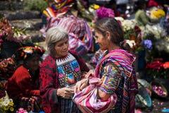 Dos mujeres locales que llevan la ropa tradicional en un mercado callejero en la ciudad de Chichicastenango, en Guatemala fotografía de archivo