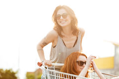 Dos mujeres locas de risa en las gafas de sol que se divierten Imagen de archivo libre de regalías