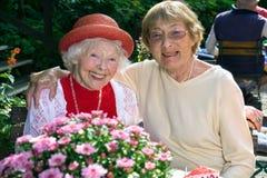Dos mujeres mayores cariñosas que gozan del café Foto de archivo libre de regalías