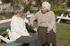 Dos mujeres mayores felices que charlan al aire libre Foto de archivo