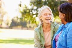 Dos mujeres mayores que hablan al aire libre junto fotografía de archivo
