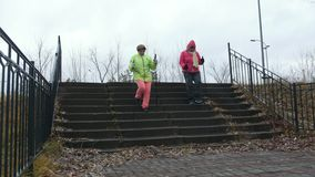 Dos mujeres mayores que hacen el nordic que camina en el parque del otoño al aire libre almacen de video