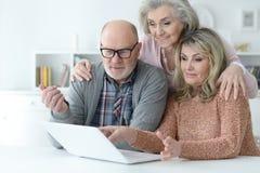 Dos mujeres mayores y hombre que usa el ordenador portátil Fotos de archivo libres de regalías