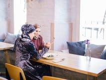 Dos mujeres musulmanes en café, hacen compras en línea usando la tableta electrónica Foto de archivo