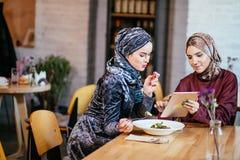 Dos mujeres musulmanes en café, hacen compras en línea usando la tableta electrónica Imágenes de archivo libres de regalías