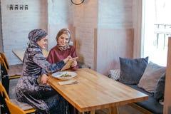 Dos mujeres musulmanes en café, hacen compras en línea usando la tableta electrónica Imagen de archivo libre de regalías