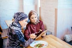Dos mujeres musulmanes en café, hacen compras en línea usando la tableta electrónica Imagenes de archivo