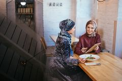 Dos mujeres musulmanes en café, hacen compras en línea usando la tableta electrónica Fotografía de archivo libre de regalías