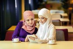 Dos mujeres musulmanes en un café, hacen compras en línea usando la tableta electrónica Fotografía de archivo libre de regalías