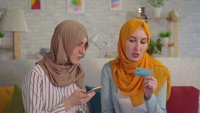 Dos mujeres musulmanes jovenes hermosas en hijabs con un teléfono y tarjetas de banco en sus manos que hablan en la sala de estar almacen de metraje de vídeo