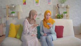 Dos mujeres musulmanes jovenes hermosas en hijabs con un teléfono y tarjetas de banco en sus manos que hablan en la sala de estar metrajes