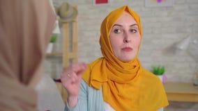 Dos mujeres musulmanes jovenes sordas hermosas en hijabs que hablan con lenguaje de signos en el cierre de la sala de estar para  almacen de metraje de vídeo