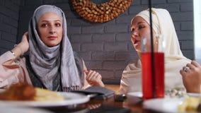 Dos mujeres musulmanes que se sientan en un restaurante y que tienen una conversación almacen de video