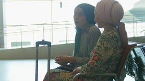 Dos mujeres musulmanes sonrientes que hablan el uno al otro en la sala de estar de aeropuertos almacen de video