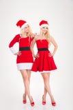 Dos mujeres positivas hermosas en Papá Noel rojo visten la presentación Foto de archivo