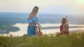 Dos mujeres preciosas que se sientan en el campo y que tienen una comida campestre - una mujer toma la cesta con el baguette y el almacen de metraje de vídeo