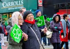 Dos mujeres presentan para la cámara en desfile del día del ` s de St Patrick en el centro de ciudad de Belfast fotos de archivo