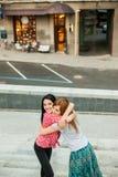 Dos mujeres que abrazan en la calle Imagen de archivo libre de regalías