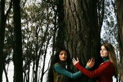 Dos mujeres que abrazan un árbol Imagen de archivo libre de regalías