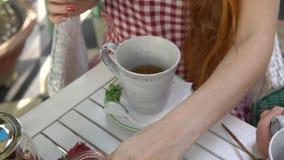 Dos mujeres que beben té Agua de colada de la mujer en la taza almacen de video