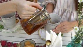 Dos mujeres que beben té Té de colada de la mujer de la tetera en la taza metrajes