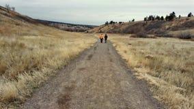 Dos mujeres que caminan abajo de un camino de tierra Imagen de archivo libre de regalías