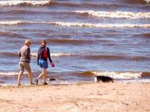 Dos mujeres que caminan un perro en la orilla de mar Báltico Fotos de archivo libres de regalías
