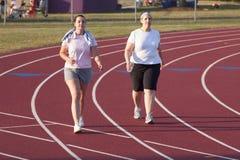 Dos mujeres que caminan una pista Imagen de archivo libre de regalías