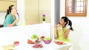 Dos mujeres que cantan con las verduras mientras que cocina divertido almacen de metraje de vídeo