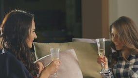 Dos mujeres que charlan, champán de consumición y sonriendo en sitio almacen de metraje de vídeo