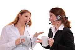 Dos mujeres que charlan con los receptores de cabeza que desgastan Fotos de archivo libres de regalías