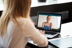 Dos mujeres que charlan en línea haciendo la llamada video en el ordenador portátil imágenes de archivo libres de regalías