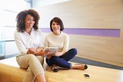 Dos mujeres que comparten una tableta, mirando a la cámara imagenes de archivo
