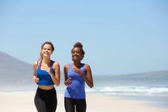 Dos mujeres que corren en la playa en verano Foto de archivo libre de regalías