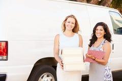 Dos mujeres que corren negocio de abastecimiento con Van Imagen de archivo libre de regalías