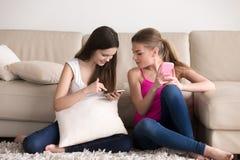Dos mujeres que descansan y que usan los teléfonos móviles en casa Fotografía de archivo libre de regalías